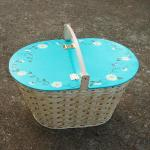 Picnic basket with hand painted aqua wooden lid surrounded with daisies and vines.